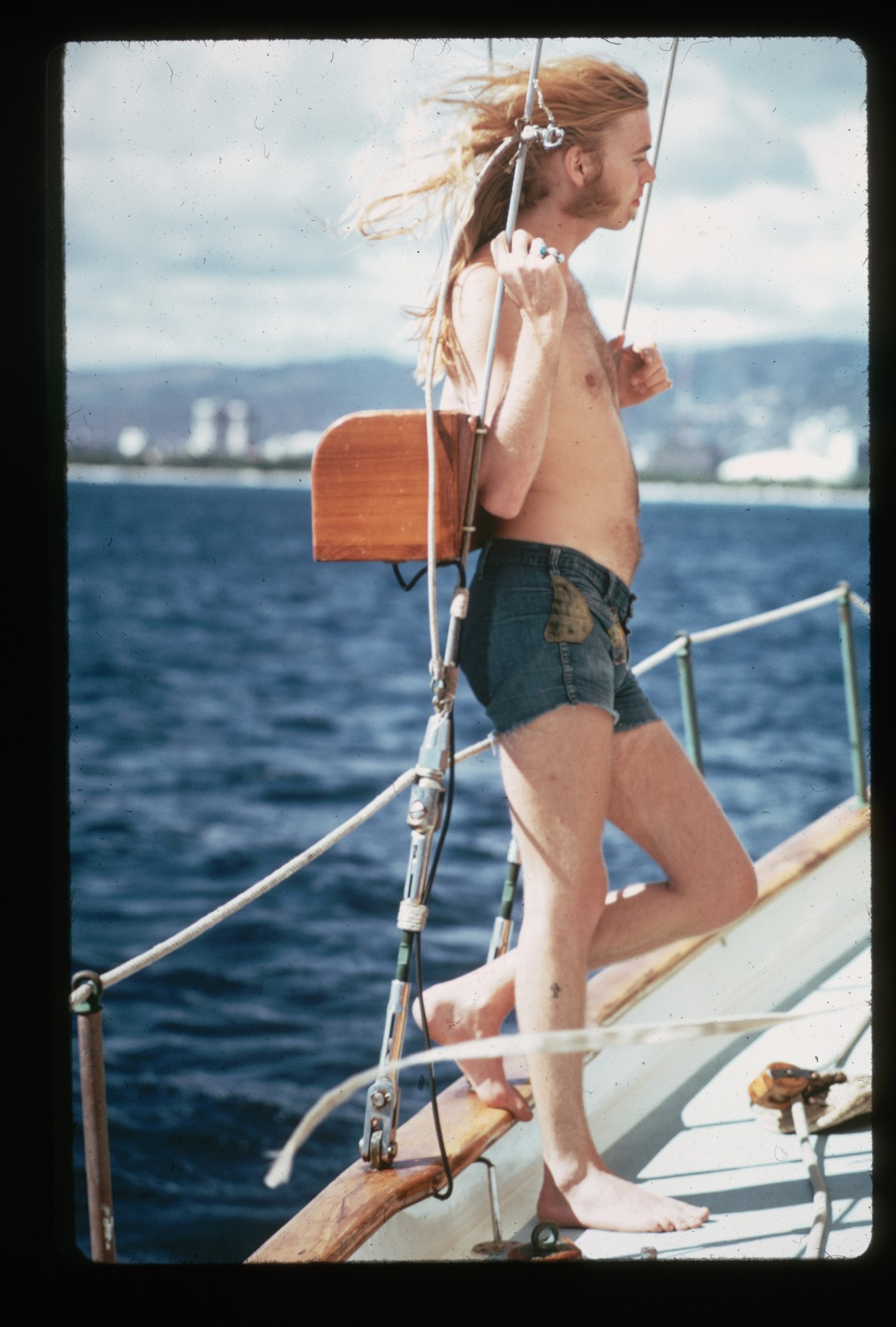 A shirtless Gregg Allman poses while leaning against the ropes on a boat in 1974.