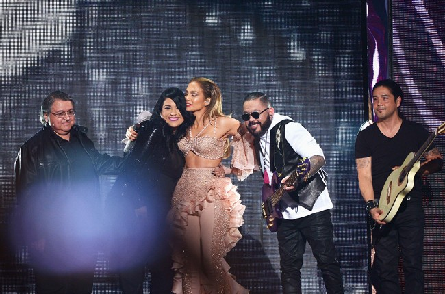 Jennifer Lopez and Los Dinos onstage after performing musical tribute to Selena at the 2015 Billboard Latin Music Awards