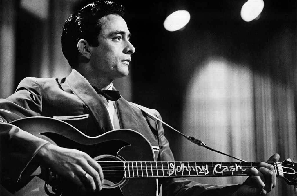 Johnny Cash performs onstage with an acoustic guitar in 1957.