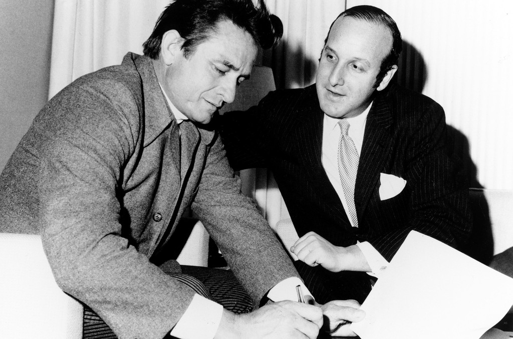 Johnny Cash signs a record contract with Columbia Records lawyer Clive Davis in circa 1960.