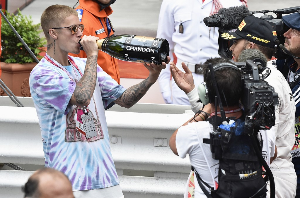 Justin Bieber drinks champagne at the F1 Grand Prix