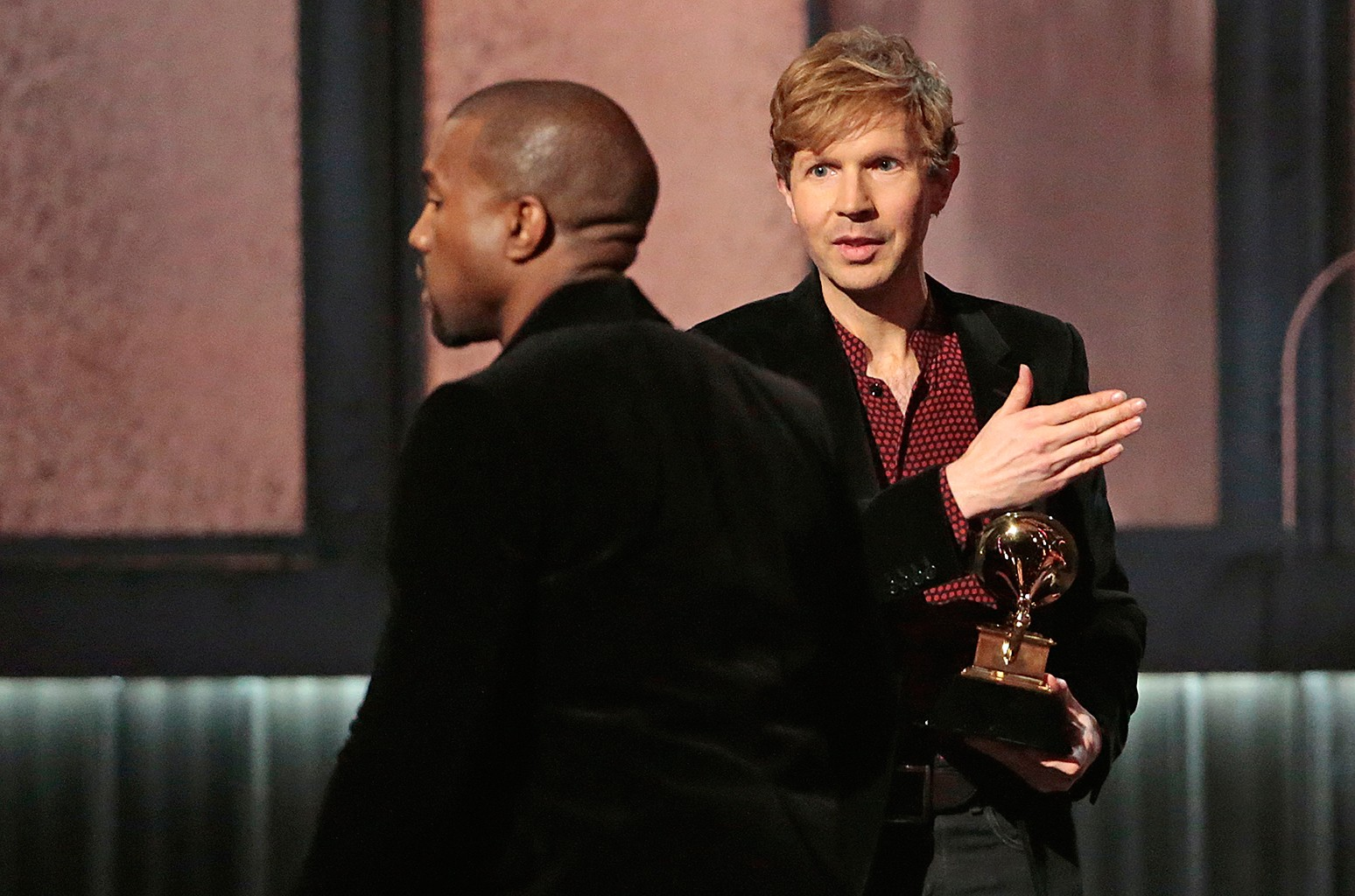 Kanye West avoids contact with an inviting Beck after Beck won Album of the Year at the 57th Annual GRAMMY Awards at Staples Center in Los Angeles on Feb. 8, 2015.