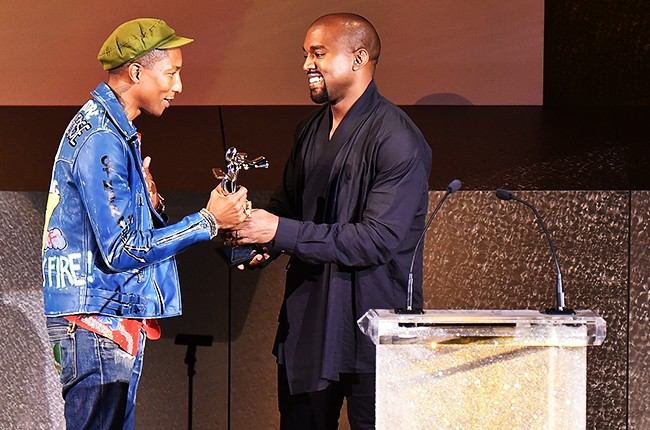 Kanye West presents the Fashion Icon Award to Pharrell Williams onstage at the 2015 CFDA Fashion Awards