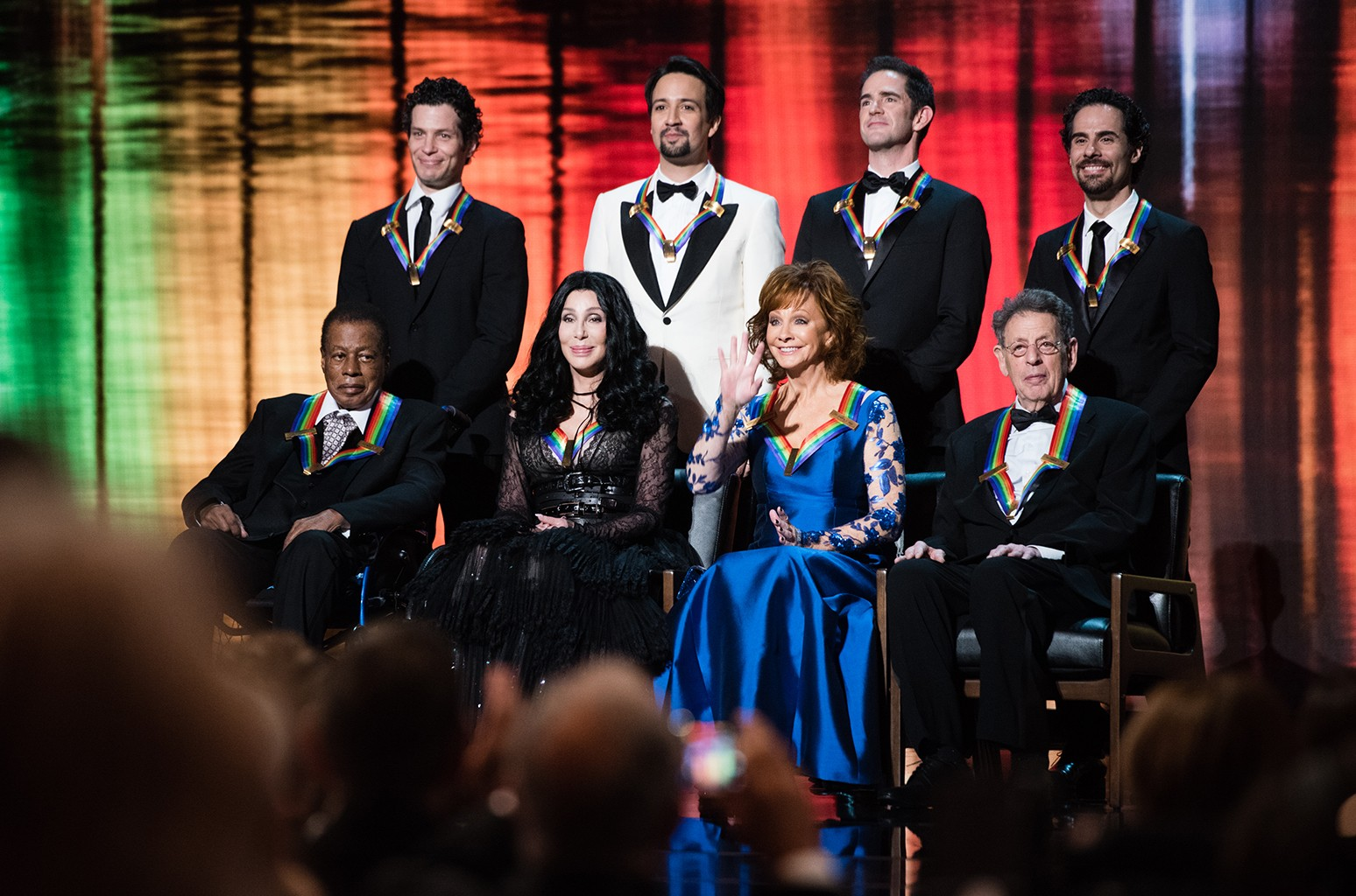 At the top of the show, the awardees are pictured on stage. In the back row are Hamilton Co-Creators Thomas Kail, Lin-Manuel Miranda, Andy Blankenbuehler, and Alex Lacamoire. In the front are Wayne Shorter, Cher, Reba McEntire, and Philip Glass.