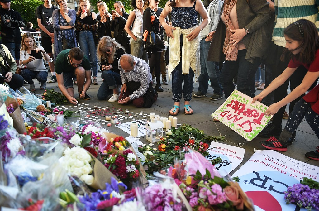People pile up flowers and arrange candles and signs at a vigil in Albert Square in Manchester on May 23, 2017.