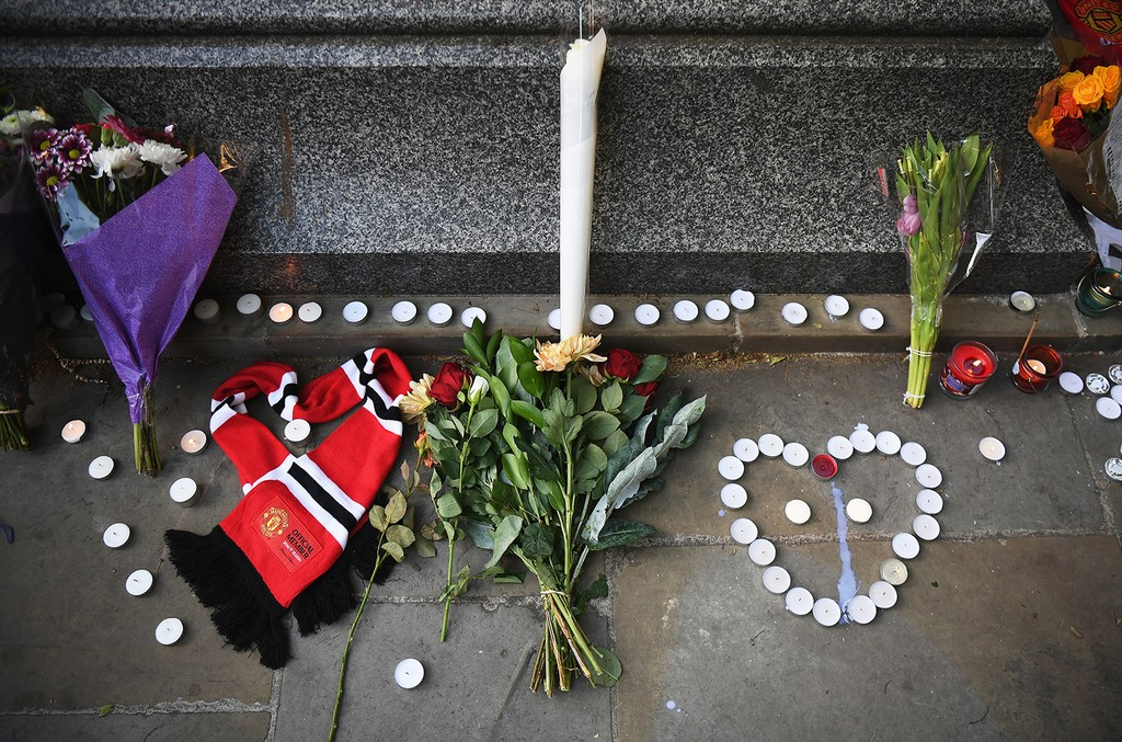 A Manchester United scarf, laid in the shape of a heart, lies next to flowers left by members of the public at a candlelit vigil to honor the victims of Monday evening's terror attack at Albert Square on May 23, 2017 in Manchester, England.