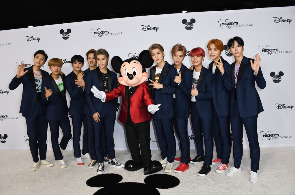 NCT 127 pose with Mickey Mouse as they attend Mickey's 90th Spectacular.