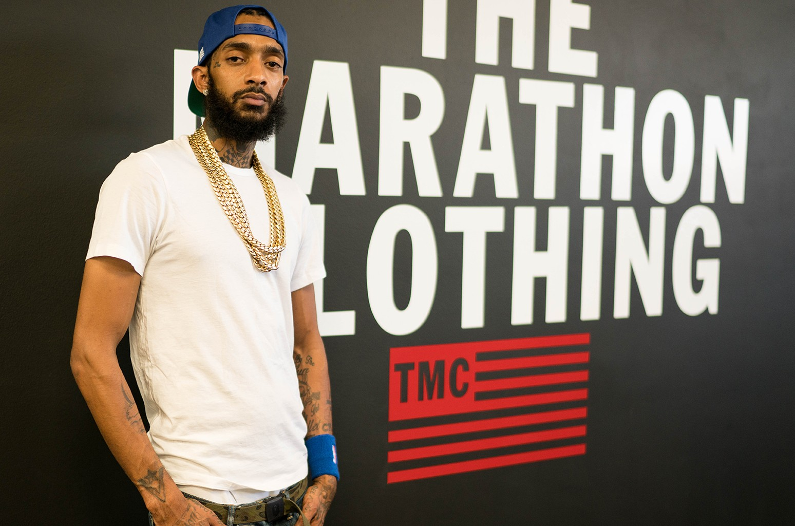 Nipsey Hussle standing in front of programmable logo design inside his new Smart Store.
