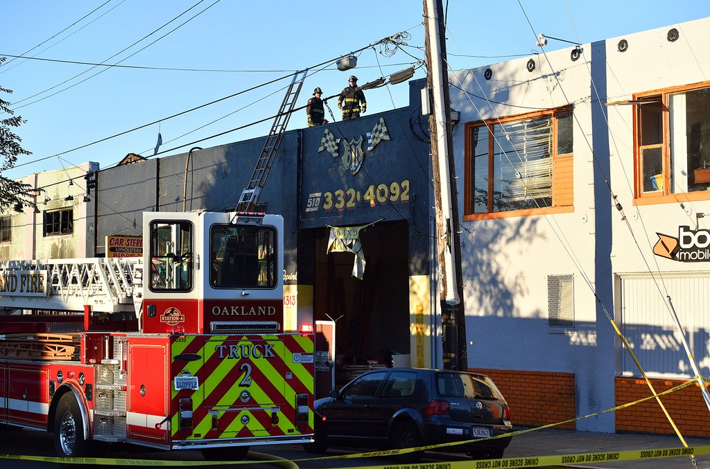 Firefighters assess the scene where a fire tore through a warehouse party early Saturday, Dec. 3, 2016 in Oakland