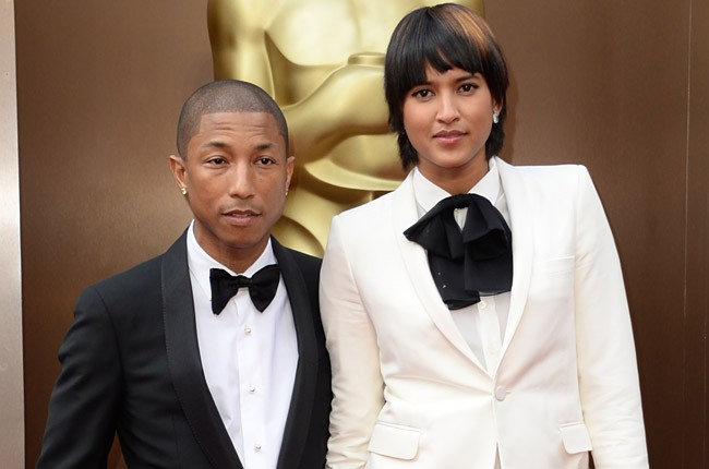Pharrell Williams (L) and Helen Lasichanh arrive on the red carpet for the 86th Academy Awards on March 2nd, 2014 in Hollywood, California. AFP PHOTO / Robyn BECK (Photo credit should read ROBYN BECK/AFP/Getty Images)