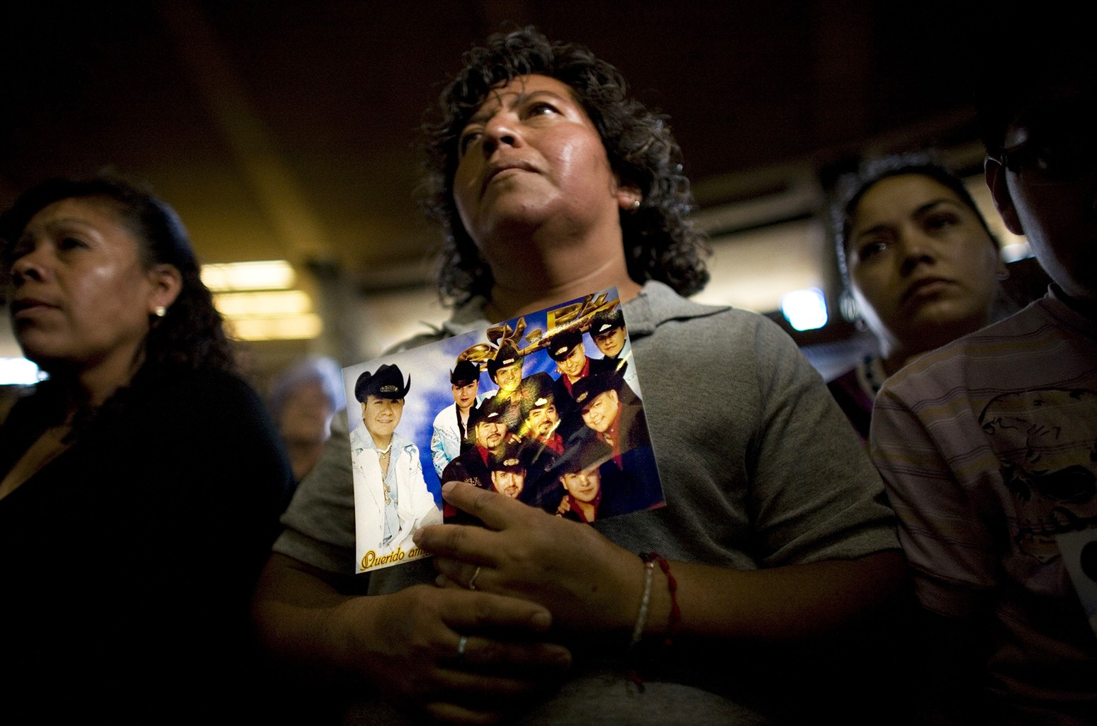 A fan holds a picture of the Mexican band K-Paz de la Sierra during a mass honoring the late Sergio Gomez, leader of the band, in Mexico City on June 2, 2008.