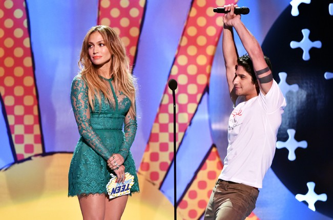 Jennifer Lopez and actor Tyler Posey onstage during FOX's 2014 Teen Choice Awards