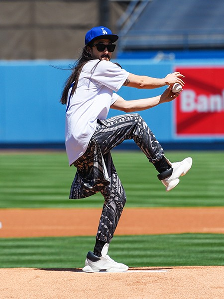 Steve Aoki throws out the ceremonial first pitch at a baseball game between the Colorado Rockies and the Los Angeles Dodgers