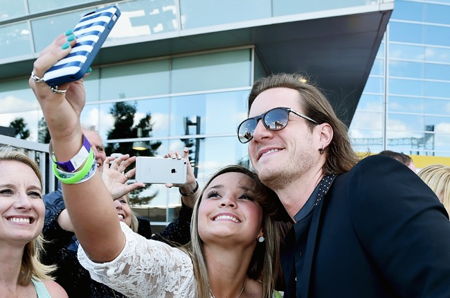 Tyler Hubbard of Florida Georgia Line poses for a selfie photo with a fan at the 50th Academy Of Country Music Awards