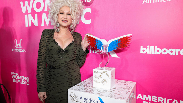 <p>Cyndi Lauper signing the American Airlines podium on the Women In Music&nbsp&#x3B;red carpet.</p>